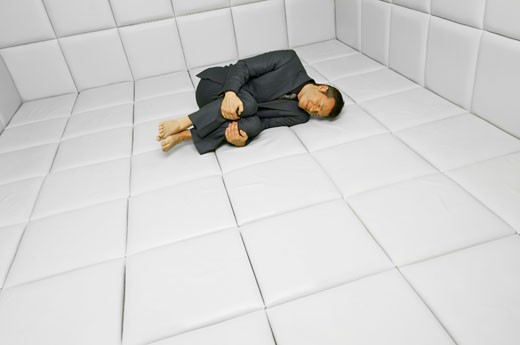 Man in Fetal Position in Padded Room    : Stock Photo