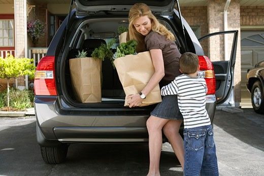 Mother and Son Removing Groceries from Car    : Stock Photo