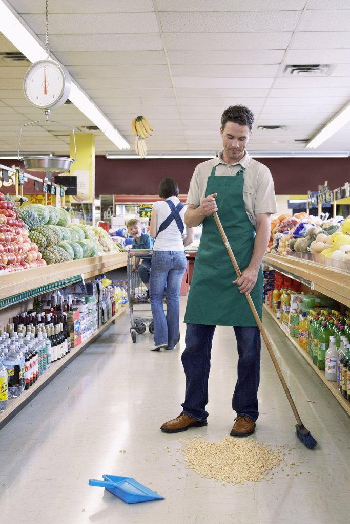 Sales Associate in Grocery Store Cleaning Aisle    : Stock Photo