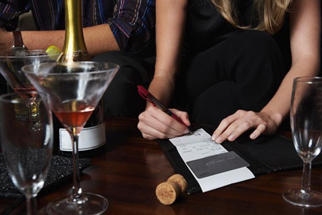 Woman Signing Bill at Bar    : Stock Photo