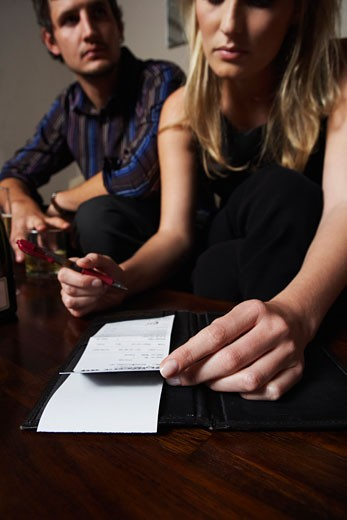 Stock Photo: 1828R-28076 Woman Signing Bill at Bar