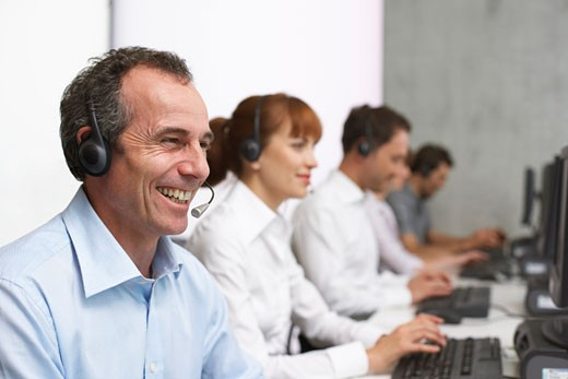 Business People Working at Computers with Headsets    : Stock Photo