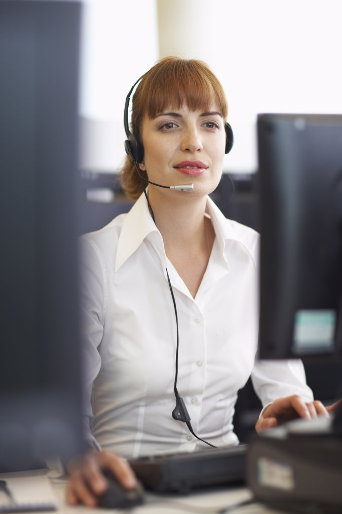Stock Photo: 1828R-28221 Businesswoman Working on Computer with Headset