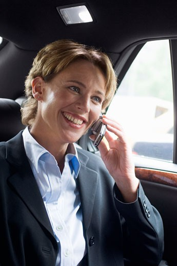 Stock Photo: 1828R-28906 Businesswoman Using Cellular Phone in Car