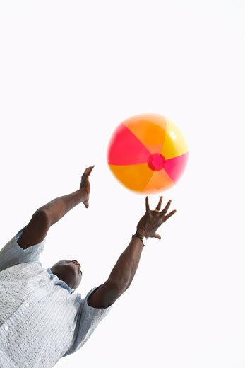 Stock Photo: 1828R-30526 Man Playing with Beach Ball