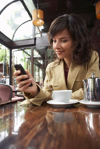 Stock Photo: 1828R-30719 Woman Using Cellphone at Cafe