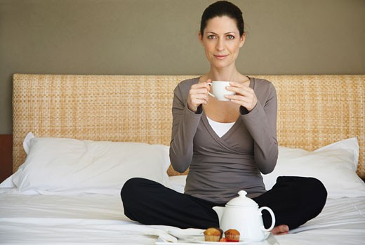 Stock Photo: 1828R-30801 Woman Having Tea on Bed