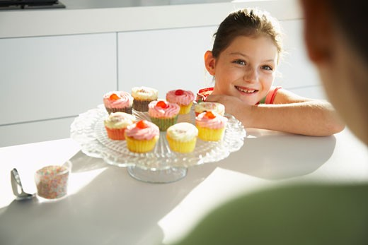Stock Photo: 1828R-30816 Daughter and Mother in Kitchen with Cupcakes