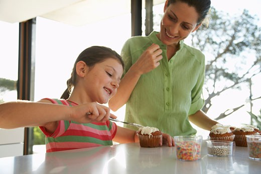 Stock Photo: 1828R-30818 Mother and Daughter Making Cupcakes