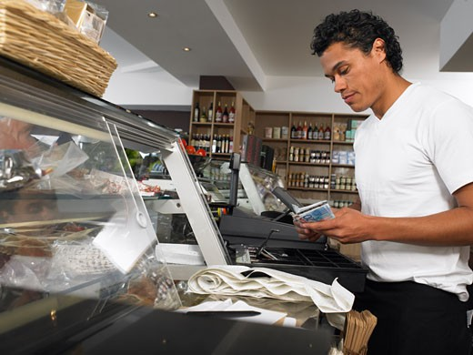 Man Counting Cash at Register    : Stock Photo