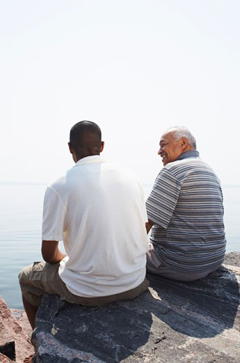 Father and Son on Rocks by Water    : Stock Photo