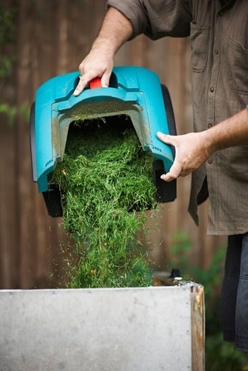 Man Emptying Grass Clippings    : Stock Photo