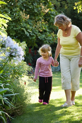 Stock Photo: 1828R-32276 Grandmother and Granddaughter Walking in Garden