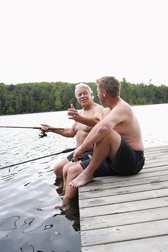 Stock Photo: 1828R-33144 Father and Son Fishing on Dock