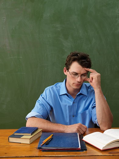Stock Photo: 1828R-33498 Teacher Reading at Desk