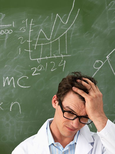 Stock Photo: 1828R-33522 Confused Scientist in Front of Blackboard