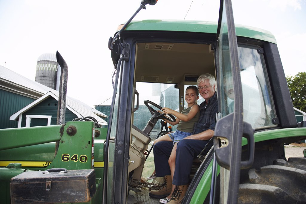 Stock Photo: 1828R-33812 Girl in Tractor with Grandfather