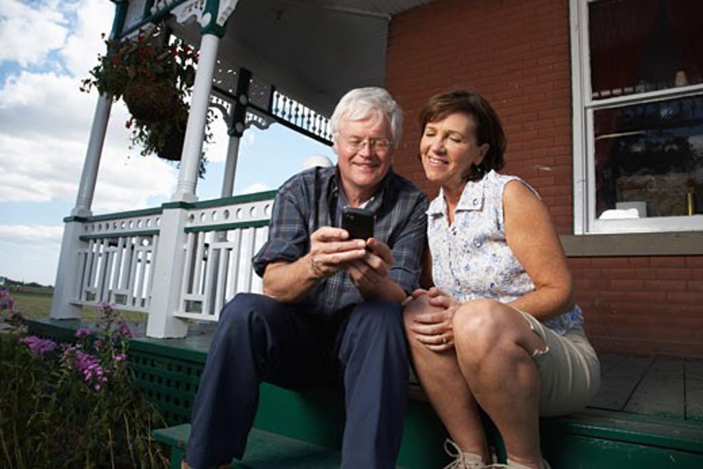 Couple with Electronic Organizer on Porch of Farmhouse    : Stock Photo