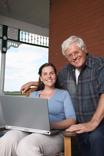 Father and Daughter with Laptop on Porch of Farmhouse    : Stock Photo