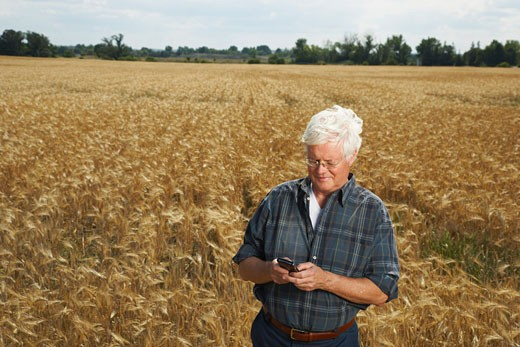 Farmer in Field with Electronic Organizer    : Stock Photo