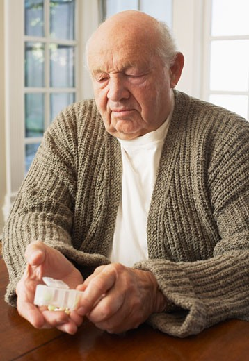 Stock Photo: 1828R-33877 Senior Man Looking at Pill Organizer