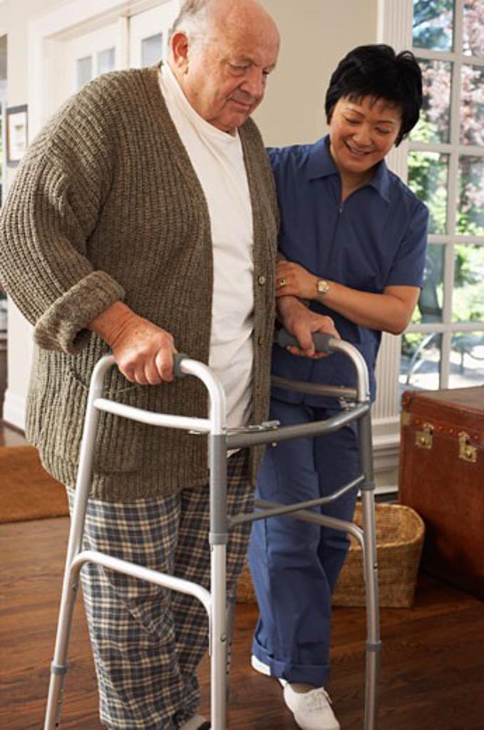 Senior Man Receiving Assistance Using Walker    : Stock Photo