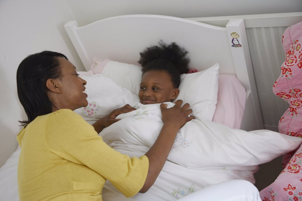 Mother Tucking Daughter into Bed    : Stock Photo