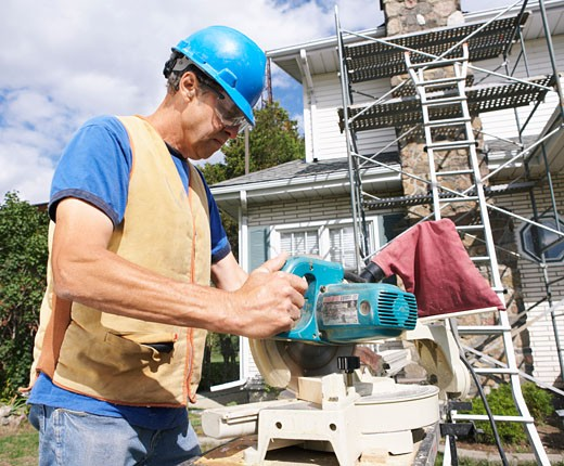 Construction Worker Cutting Wood    : Stock Photo