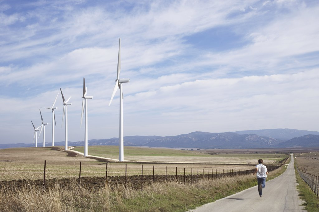 Boy Running on Rural Raod, next to Wind Turbines    : Stock Photo