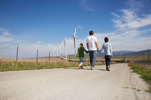 Stock Photo: 1828R-34959 Father and Children Walking on Rural Road, next to Wind Turbines