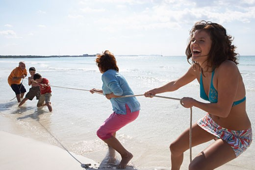 Stock Photo: 1828R-35068 Family Playing Tug-of-War on the Beach