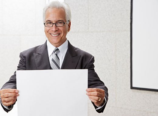 Stock Photo: 1828R-36021 Businessman Holding Blank Piece of Paper
