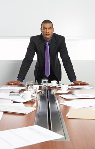 Stock Photo: 1828R-36457 Businessman at Messy Boardroom Table