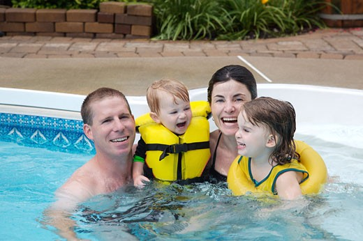Family in Backyard Swimming Pool    : Stock Photo