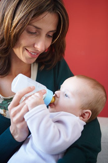 Mother Feeding Baby with Bottle    : Stock Photo