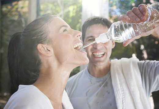 Stock Photo: 1828R-38451 Man Squirting Water into Woman's Mouth