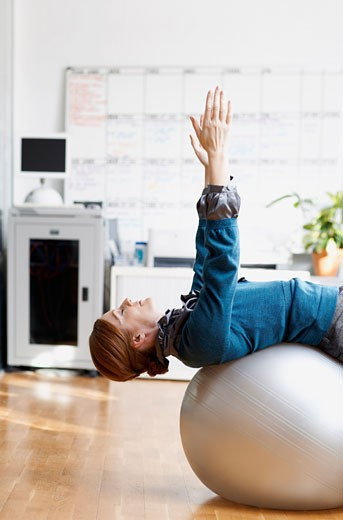 Woman using Exercise Ball in Office    : Stock Photo
