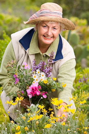 Stock Photo: 1828R-41117 Portrait of Woman in Meadow, Collecting Flowers