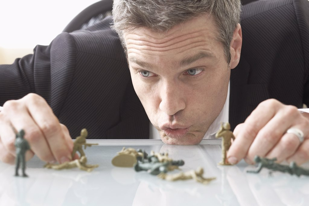Stock Photo: 1828R-42066 Businessman Playing with Toy Soldiers on Desk