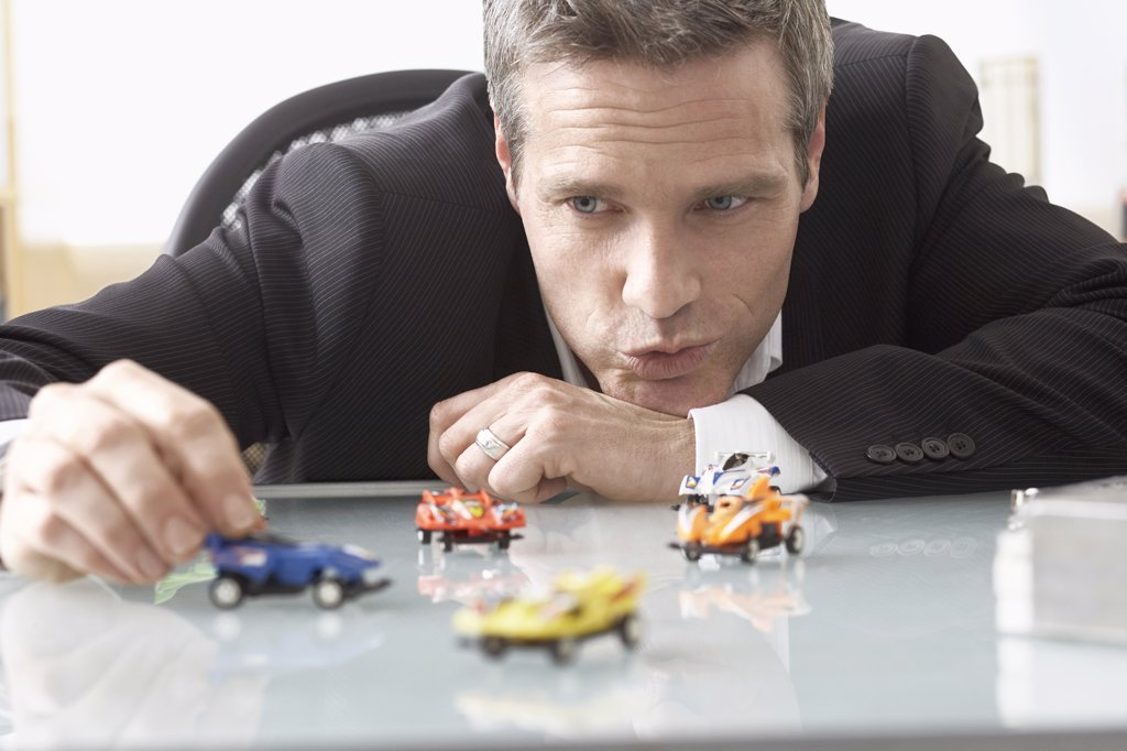 Stock Photo: 1828R-42070 Businessman Playing with Toy Race Cars on Desk