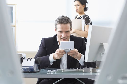 Co-worker looking at Businessman Playing Handheld Video Game at Desk    : Stock Photo