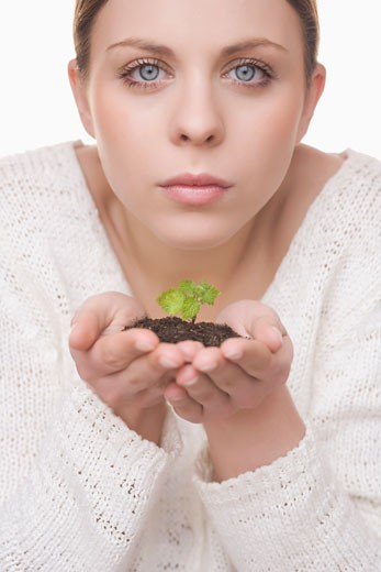 Stock Photo: 1828R-44938 Woman Holding Plant in Soil