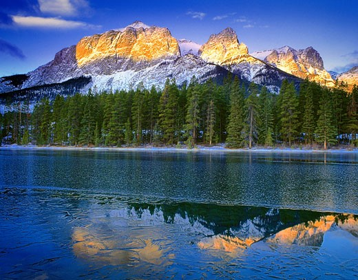 Stock Photo: 1828R-4588 Sunrise over Mountains, Trees And Lake in Winter, Near Canmore, Alberta, Canada
