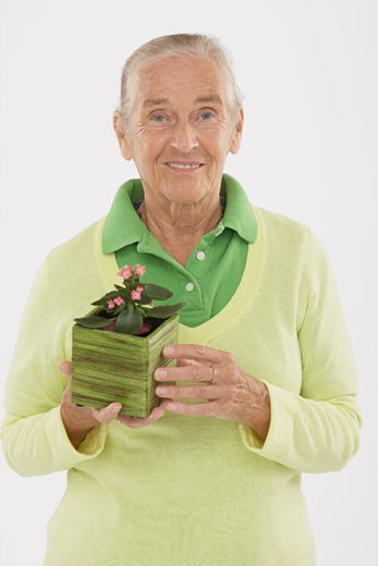 Stock Photo: 1828R-46178 Portrait of Woman Holding Potted Plant