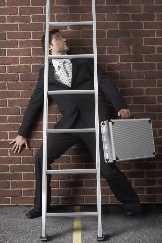 Stock Photo: 1828R-46711 Businessman Walking Under Ladder