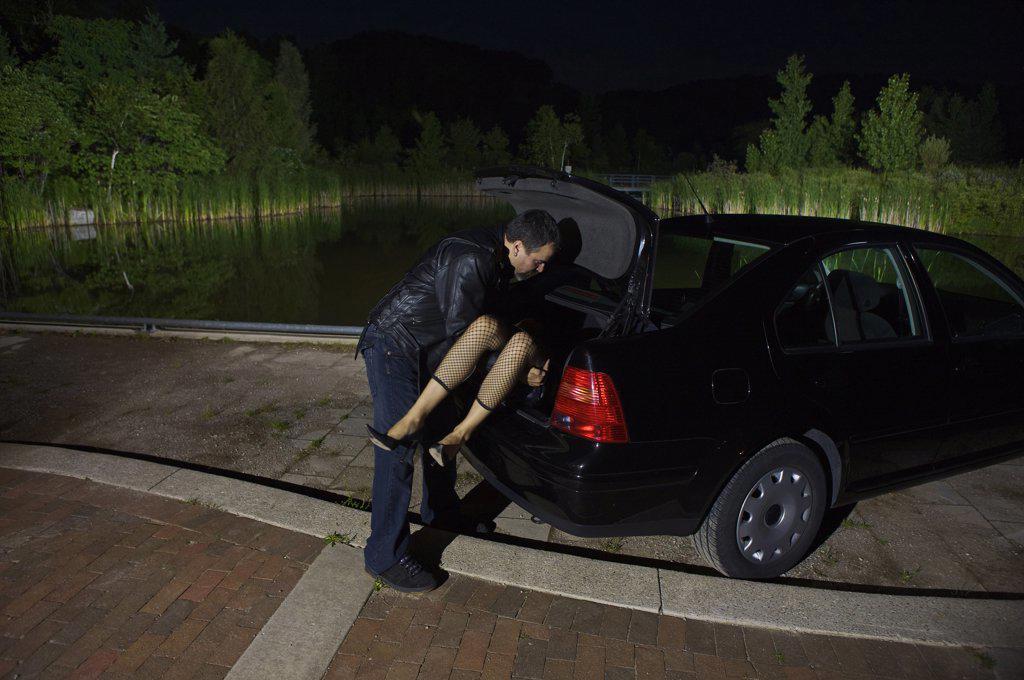 Stock Photo: 1828R-47457 Man Disposing of Woman's Body