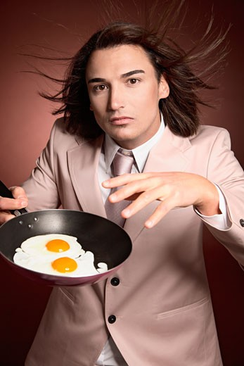 Man Holding Frying Pan with Eggs    : Stock Photo