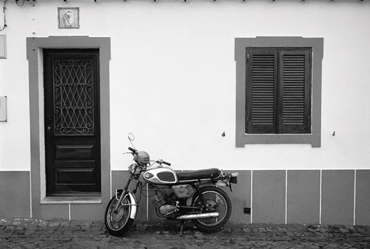 Stock Photo: 1828R-4818 Motorcycle Parked near Door, Portugal