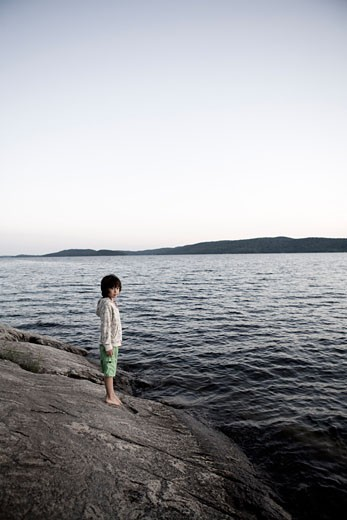 Stock Photo: 1828R-48354 Boy on Rocky Shoreline, Sandbanks Provincial Park, Prince Edward County, Ontario