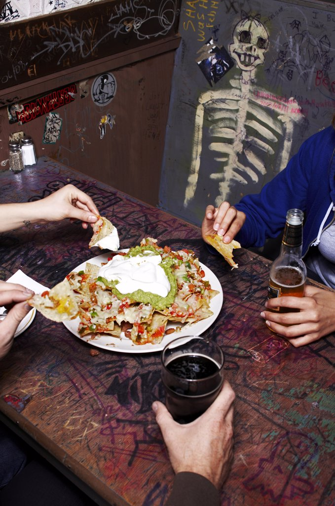 Group of People in Restaurant Eating Nachos and Drinking Beer    : Stock Photo